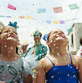 Two girls (5-9) standing under falling confetti at fiesta