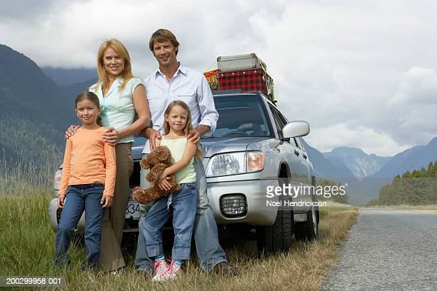Two girls (6-8 years) standing with parents beside car on rural grass verge, portrait
