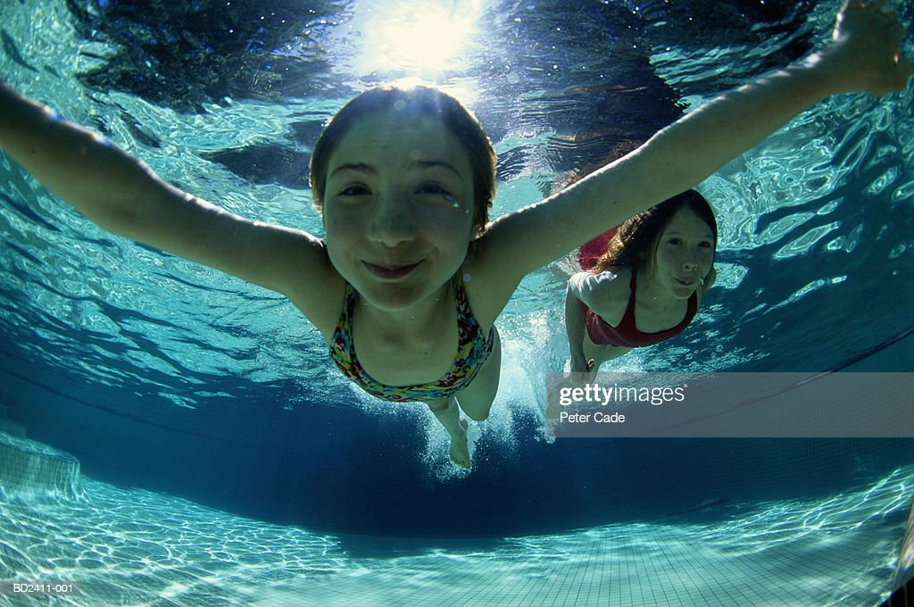 Two girls (10-12) swimming underwater, low angle view : Stock Photo