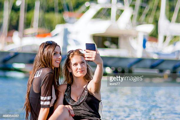 Two girls taking a selfie at a marina
