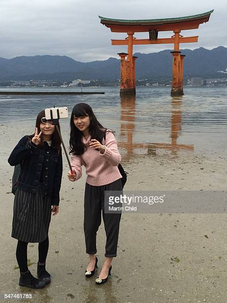 Two girls taking a selfie in front of the floating Torii gate on The island of Miyajima in Japan