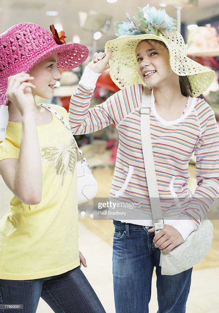 Two girls trying on hats in store : Stock Photo
