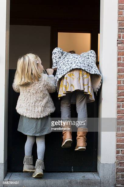 Two girls trying to climb over a door