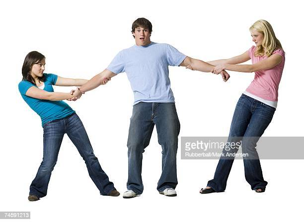 Two girls tugging at arms of boy