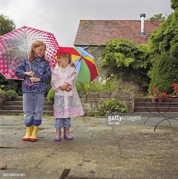 Two girls (5-7) under umbrellas in garden
