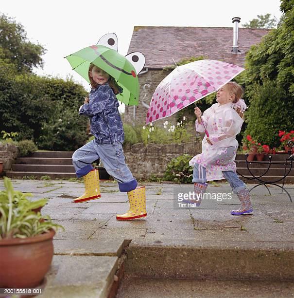 Two girls (5-7) under umbrellas, skipping through garden