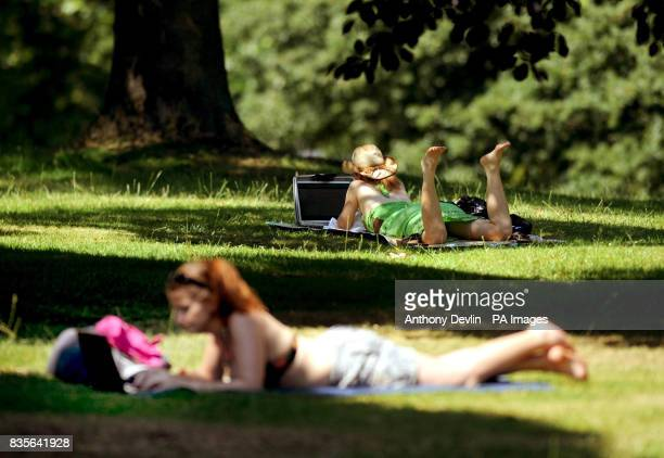 Two girls use laptops as people enjoy the sunshine on Primrose Hill London
