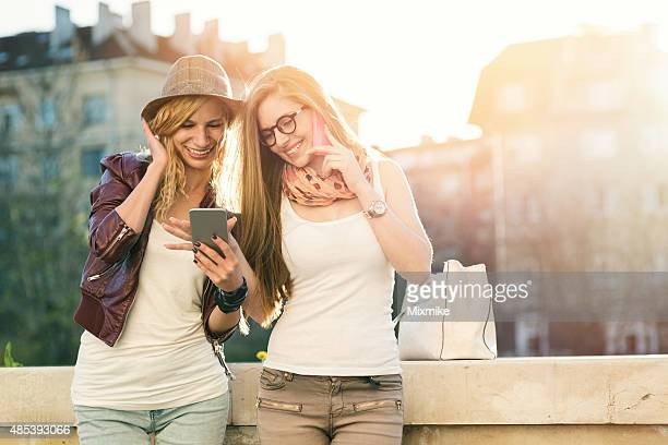 Two girls using cell phones in the city