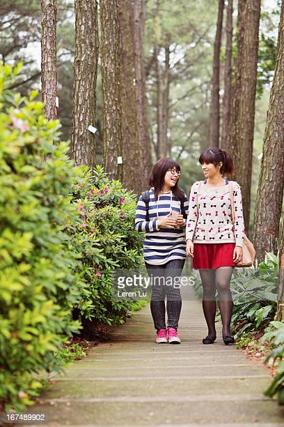 Two girls wailking and talking on footpath