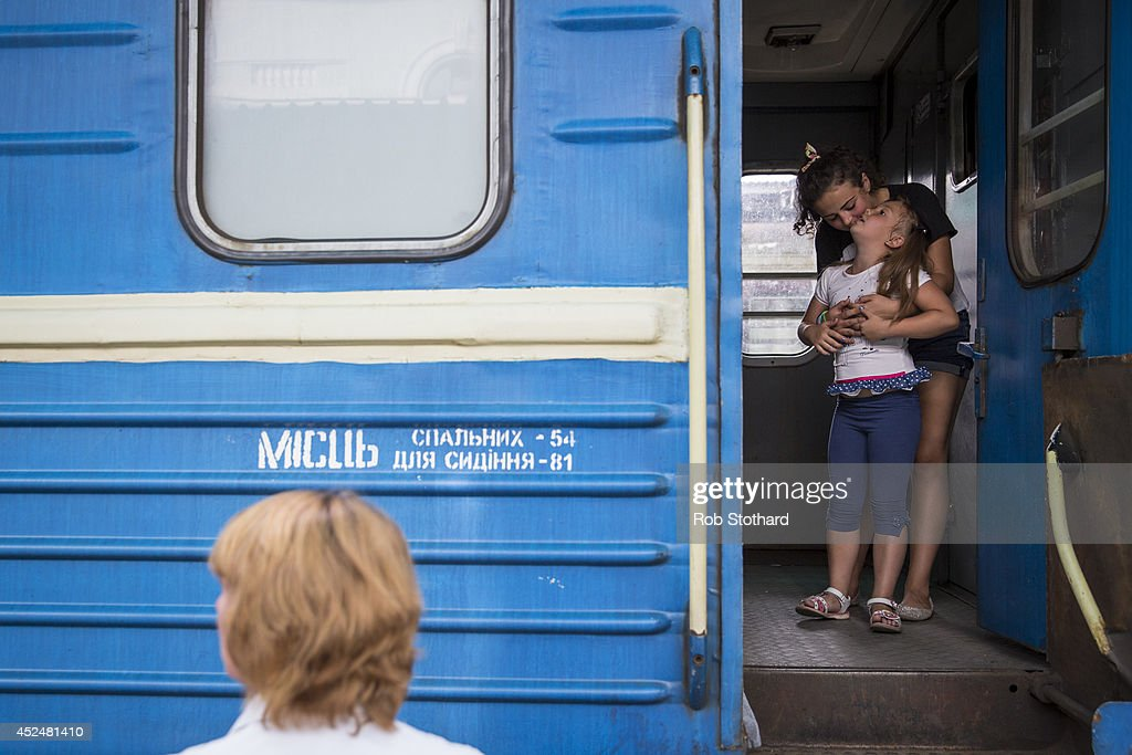Two girls wait for the train for Sevastopol to leave from the central railway station on July 21, 2014 in Donetsk, Ukraine. Local authorities warned residents in the area not to go outside or leave their homes whilst intense shelling set a market ablaze close to the station. The security situation is continuing to affect the investigation into the Malaysian Airlines flight MH17 crash and it is still unclear where or when the train containing the bodies of victims will be moved. Malaysian Airlines flight MH17 was travelling from Amsterdam to Kuala Lumpur when it crashed killing all 298 on board including 80 children. The aircraft was allegedly shot down by a missile and investigations continue over the perpetrators of the attack.