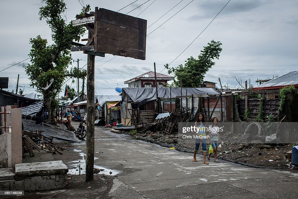 Two girls walk past a basketball hoop on April 16, 2014 in Tanauan, Leyte, Philippines. Basketball is the most popular sport in the Philippines. In the aftermath of Superstorm Yolanda that struck the coast on November 8, 2013 leaving more than 6000 dead and many more homeless, basketball hoops were some of the first things to be repaired and rebuilt amongst the rubble, showing the Filipino's resilience and intense love for the sport. Five months after the storm, basketball courts have re-emerged in large numbers across the damaged provinces using any available space and many being rebuilt from storm debris.