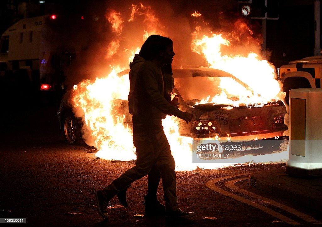Two girls walk past a burning car left following violence between, loyalists, nationalists and the police in east Belfast, Northern Ireland on January 12, 2013 after the latest loyalist march against the decision to limit the days on which the Union Flag would be flown over Belfast City Hall. Northern Irish demonstrators loyal to Britain clashed with nationalists and police on Saturday in fresh protests against curbs on flying the British flag, leaving four officers injured, police said. The clashes were the latest to blight the British province after more than five weeks of violent disorder over the flag issue.