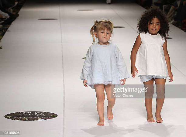 Two girls walk the runway wearing Lina Cantillo during Colombiamoda 2010 at Plaza Mayor on July 27 2010 in Medellin Colombia