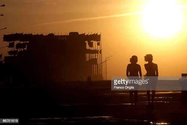 Two girls walk towards the building of the US Interests Section at the Malecon seafront during the sunset on April 27 2009 in Havana Cuba While there...