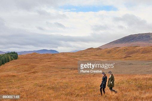 Two girls walking in landscape