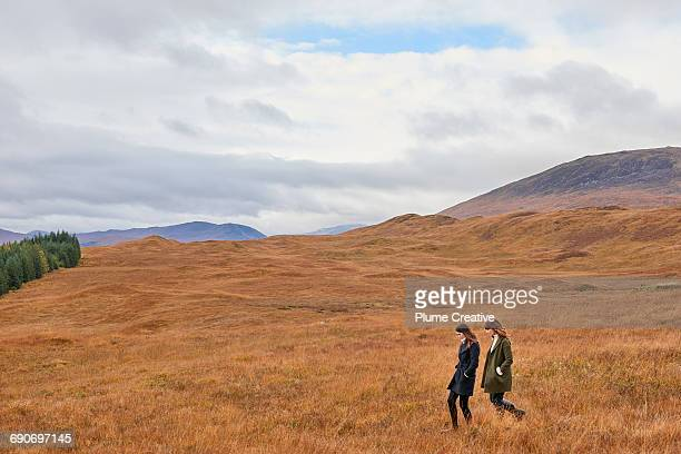 Two girls walking in landscape