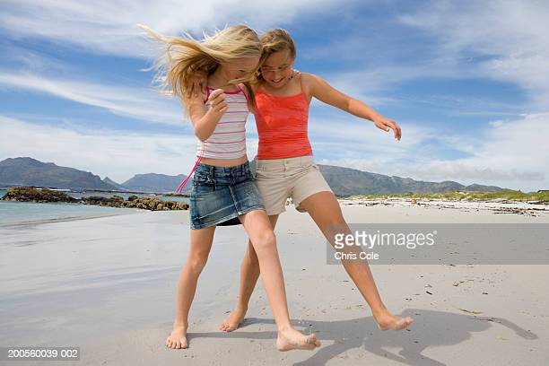Two girls (12-13) walking on beach, arm around