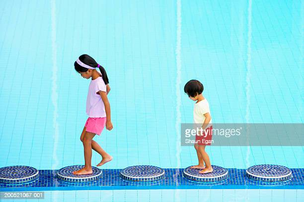 Two girls (3-6) walking on stepping stones in swimming pool