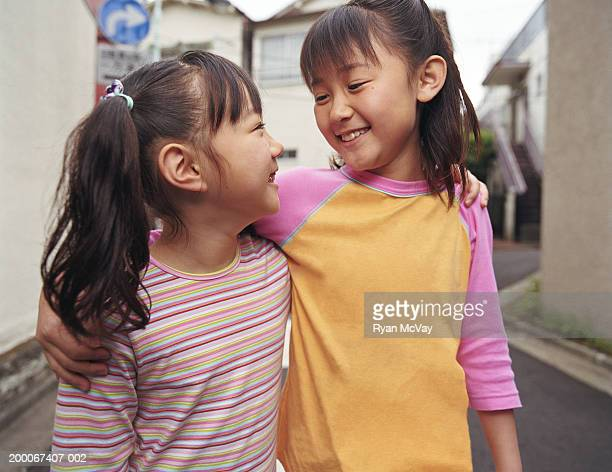 Two girls (6-9) walking with arms around one another, smiling