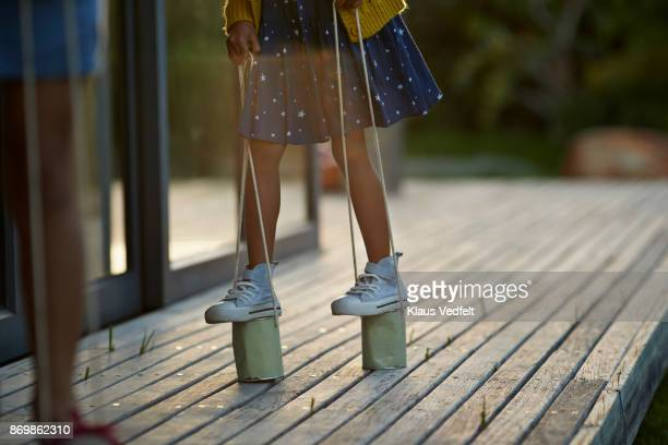 Two girls walking with can stilts on wooden terrace