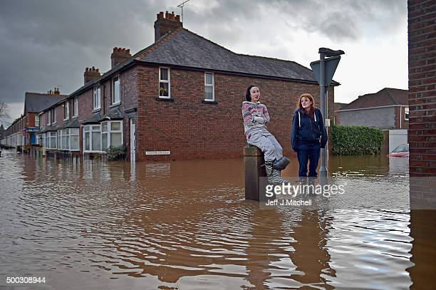 Two girls watch rescue workers checking properties as teams continue to evacuate people from their homes after Storm Desmond caused flooding on...