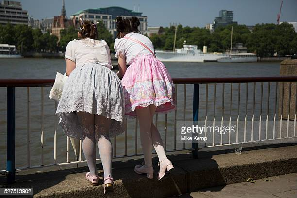 Two girls wearing Lolita dresses lean over the barrier over the River Thames on the South Bank London UK Lolita fashion is a subculture originating...