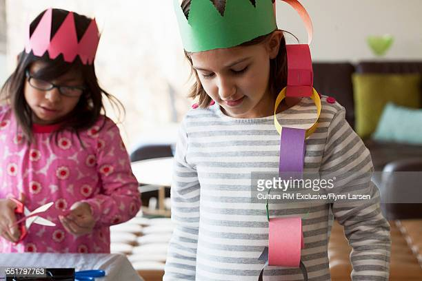 Two girls wearing paper crowns with paper chains