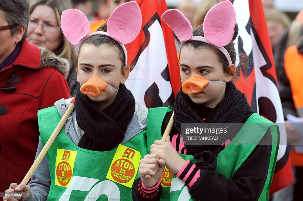 Two girls wearing pig's masks take part with Striking workers of the GAD SAS Lampaul slaughterhouse in a demonstration in Landivisiau, western France, on March 16, 2013, against the closure of their company placed under judicial receivership in February 2013.