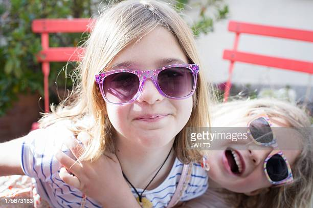 two girls wearing sunglasses, smiling to camera