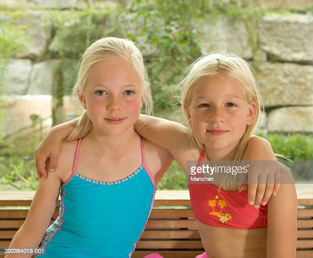 Two girls (8-10) wearing swimsuits and arms around shoulders, portrait