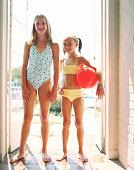 Two girls (9-12) wearing swimsuits, standing in doorway, portrait