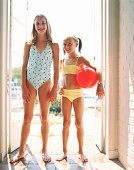 Two girls (9-12) wearing swimsuits, standing in doorway, portrait