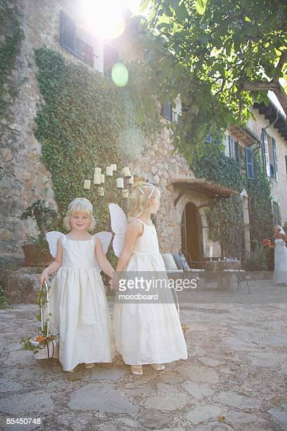 Two girls wearing wings outdoors