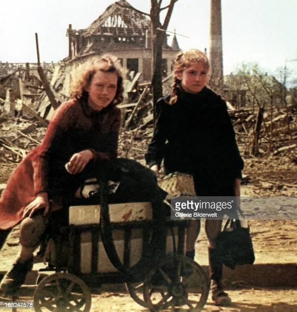 Two girls with a handcart are pausing amid the ruins of the city July 1945 More than 300 bombardments by the British Royal Air Force and the United...