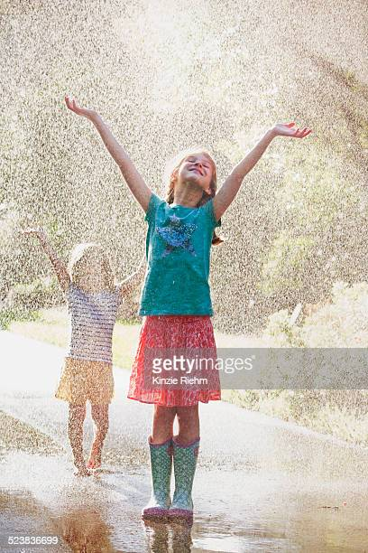 Two girls with arms open standing in water spray on street
