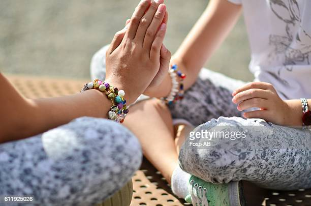 Two girls with bracelet playing clapping game