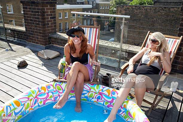 Two girls with feet in kiddie pool