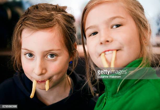 Two girls with french fries in mouths
