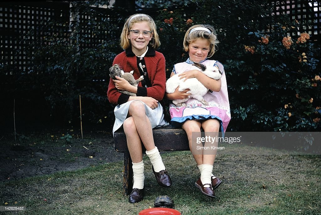 Two girls with pet rabbits : Stock Photo