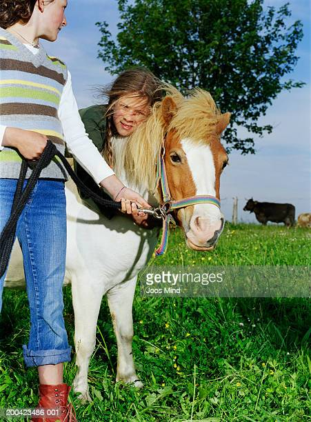 Two girls (9-11) with shetland pony, outdoors