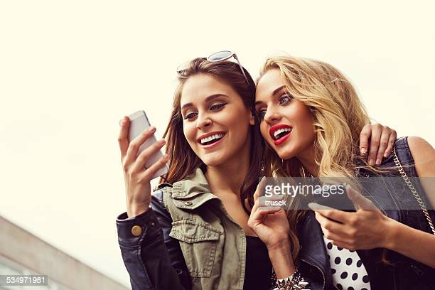 Two girls with smartphone against sky