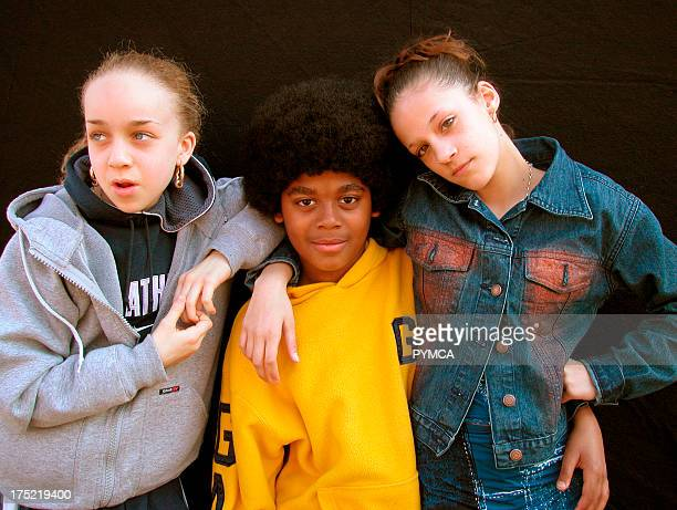 Two girls with their arms round a young boy with an afro London 2000's
