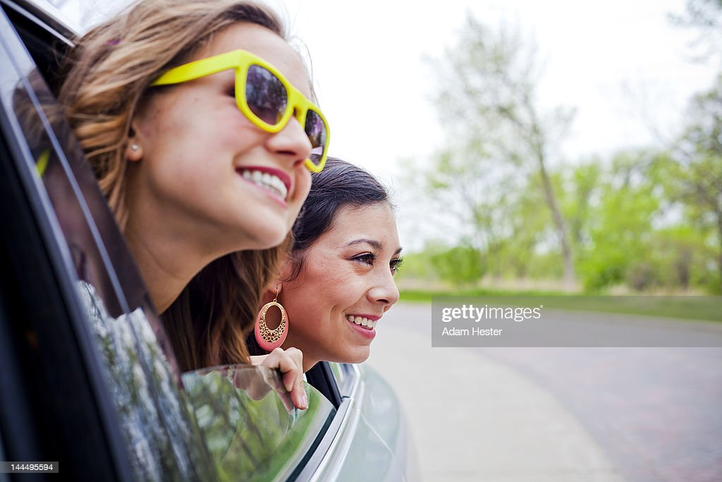 Two girls with their heads out of a car window : Stock Photo