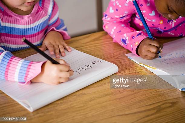 Two girls (5-7) writing at desks in classroom, mid section