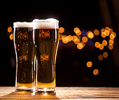 Two glasses of beer on wooden table and bar lights background.