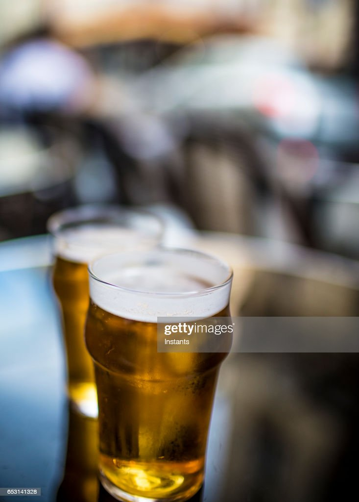 Two glasses of blonde beer on a table, shot on a Parisian cafe bar sidewalk. : ストックフォト
