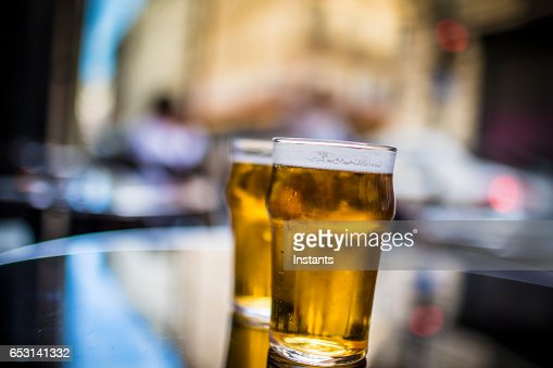 Two glasses of blonde beer on a table, shot on a Parisian cafe bar sidewalk. : Photo