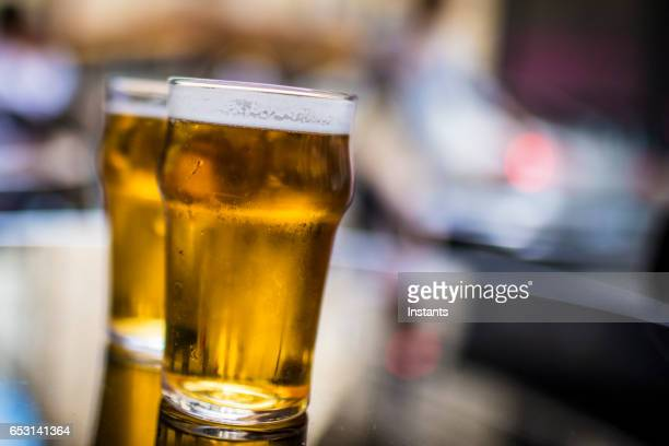 Two glasses of blonde beer on a table, shot on a Parisian cafe bar sidewalk.