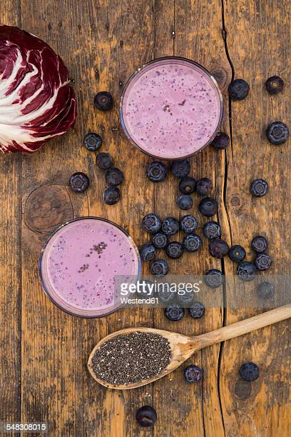 Two glasses of blueberry radicchio smoothie and wooden spoon with chia seeds