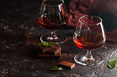 Two glasses of brandy or cognac and bottle with chocolate on dark background.